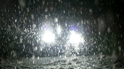 stock-footage-snow-falls-on-the-road-in-the-headlights